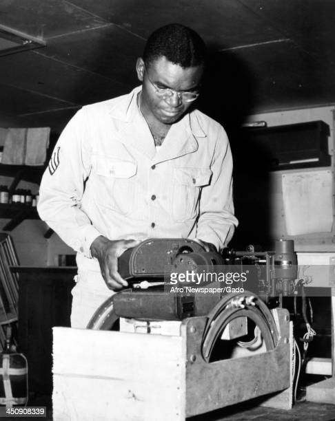 During World War 2, African American soldier Joseph Gray adjusts a bombardier training camera, December 13, 1944.