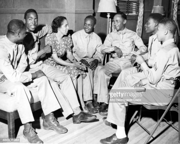 During World War 2, African American soldiers speak with Evelyna Forney at a USO club, 1942.
