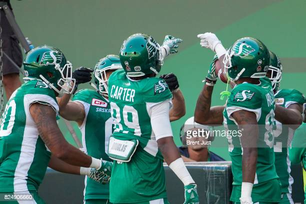 Duron Carter and Caleb Holley of the Saskatchewan Roughriders celebrate with teammates after a touchdown in the game between the Toronto Argonauts...