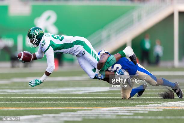 Duron Carter of the Saskatchewan Roughriders is brought down after making a catch in the preseason game between the Winnipeg Blue Bombers and...