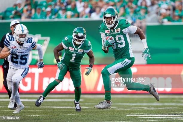 Duron Carter of the Saskatchewan Roughriders runs past Matt Webster of the Toronto Argonauts while returning a kick in the game between the Toronto...