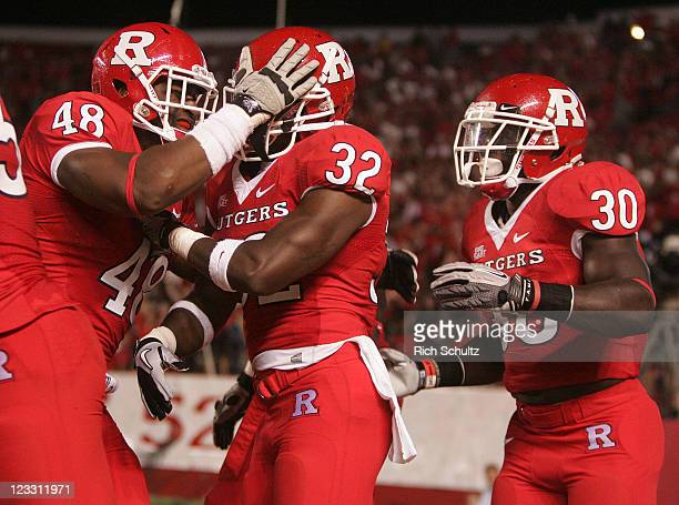 Duron Harmon of Rutgers Scarlet Knights is congratulated by teammates Marcus Thompson and Ben Martin after Harmon returned an interception for a...