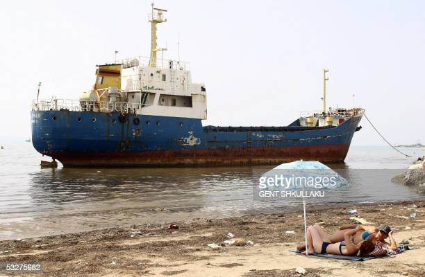 Two girls enjoy their sun bath near an abandoned ship on a beach in the Albanian Adriatic sea in the city of Durres 23 July 2005 Hot weather...