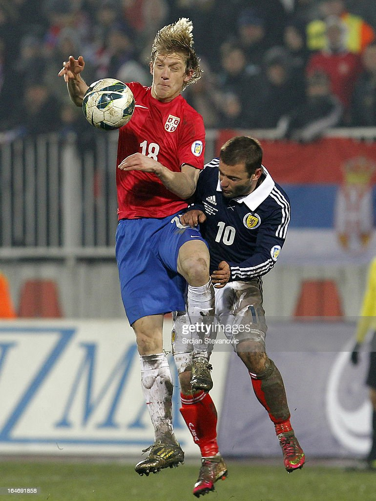 Dusan Basta (L) of Serbia jumps for the ball against Shaun Maloney (R) of Scotland during the FIFA 2014 World Cup Qualifier match between Serbia and Scotland at Karadjordje Stadium on March 26, 2013 in Novi Sad, Serbia