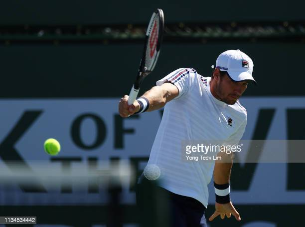 Dusan Lajovic of Serbia plays a backhand against Taro Daniel of Japan during their men's singles first round match on Day 5 of the BNP Paribas Open...