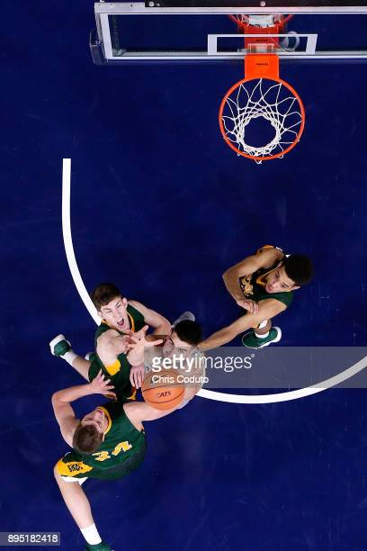 Dusan Ristic of the Arizona Wildcats fights for a rebound with Rocky Kreuser, Chris Quayle and Cameron Hunter of the North Dakota State Bison during...