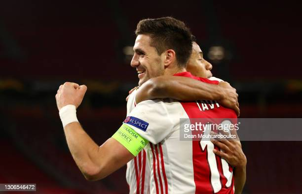 Dusan Tadic of Ajax celebrates with teammate David Neres after scoring their team's second goal during the UEFA Europa League Round of 16 First Leg...