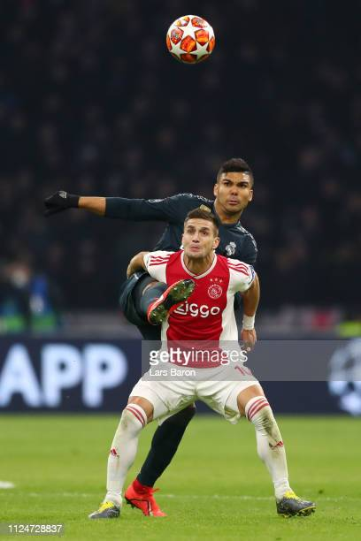 Dusan Tadic of Ajax is challenged by Casemiro of Real Madrid during the UEFA Champions League Round of 16 First Leg match between Ajax and Real...