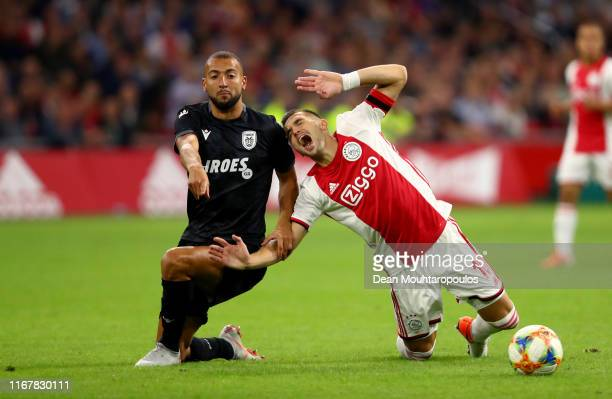 Dusan Tadic of Ajax is tackled by Omar El Kaddouri of PAOK during the UEFA Champions League Third Qualifying Round match between Ajax and PAOK...