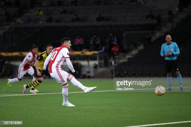 Dusan Tadic of Ajax scores their side's second goal from the penalty spot during the UEFA Europa League Round of 16 Second Leg match between BSC...