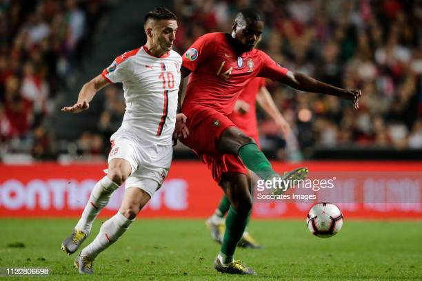 Dusan Tadic of Serbia William Carvalho of Portugal during the EURO Qualifier match between Portugal v Serbia at the Estádio da Luz on March 25 2019...