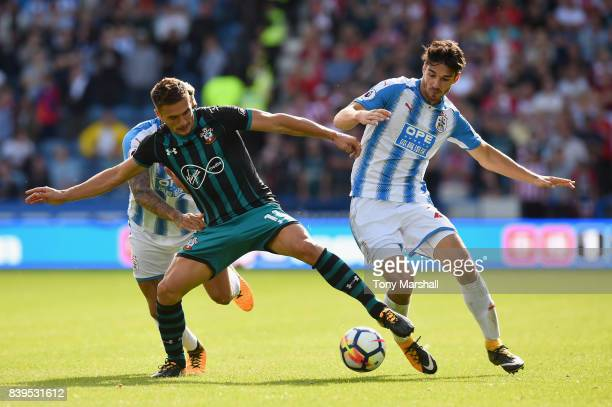 Dusan Tadic of Southampton and Christopher Schindler of Huddersfield Town battle for possession during the Premier League match between Huddersfield...