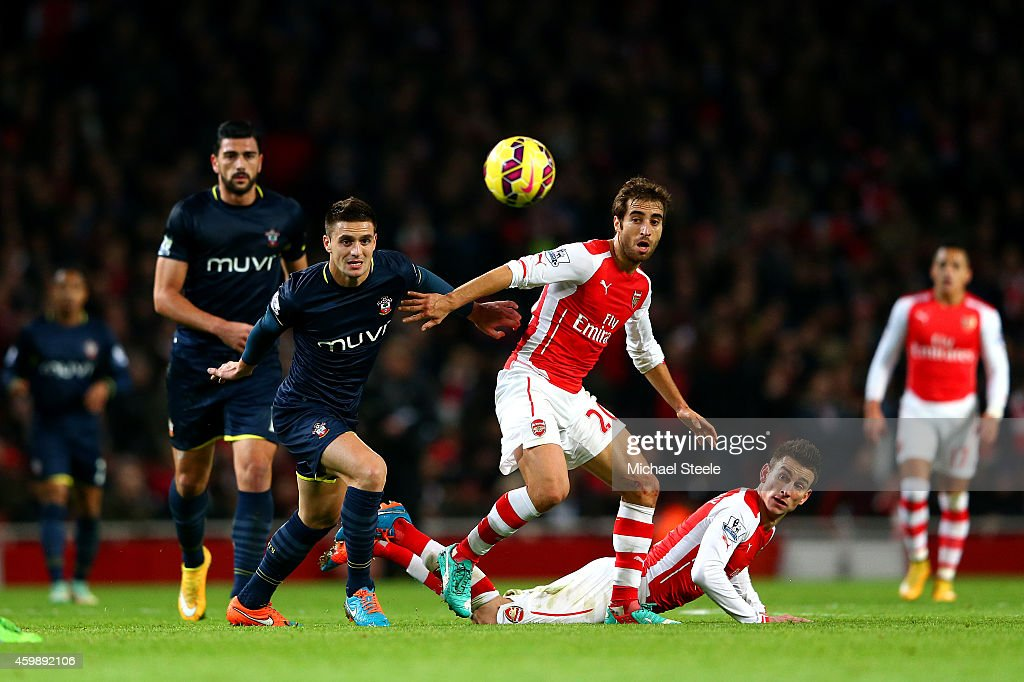 Dusan Tadic of Southampton battles for the ball with Mathieu Flamini and Laurent Koscielny of Arsenal during the Barclays Premier League match between Arsenal and Southampton at Emirates Stadium on December 3, 2014 in London, England.