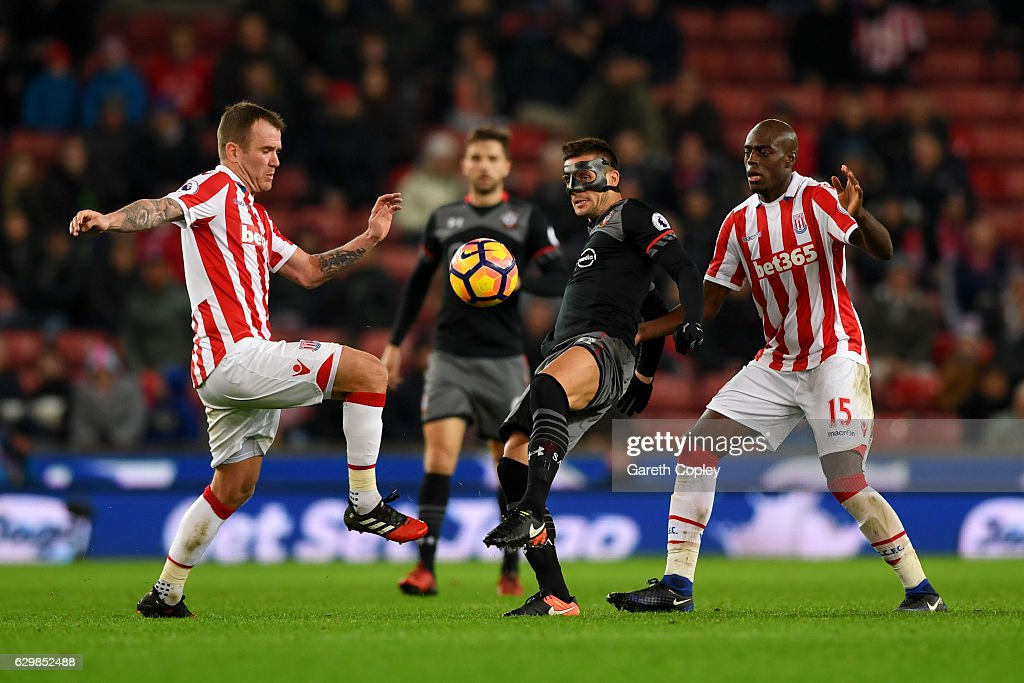 Dusan Tadic (C) of Southampton controls the ball under pressure of Charlie Adam (L) and Bruno Martins Indi (R) of Stoke City during the Premier League match between Stoke City and Southampton at Bet365 Stadium on December 14, 2016 in Stoke on Trent, England.