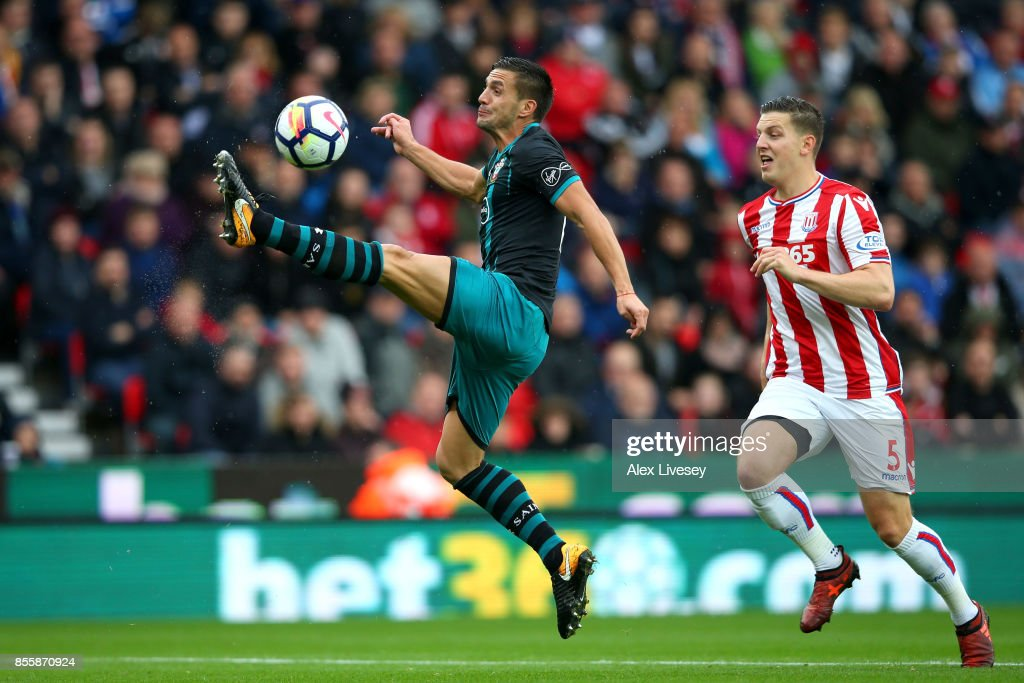 Dusan Tadic of Southampton controls the ball while under pressure from Kevin Wimmer of Stoke City during the Premier League match between Stoke City and Southampton at Bet365 Stadium on September 30, 2017 in Stoke on Trent, England.