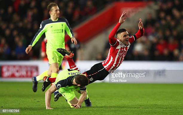 Dusan Tadic of Southampton is challenged by James Milner of Liverpool during the EFL Cup semifinal first leg match between Southampton and Liverpool...