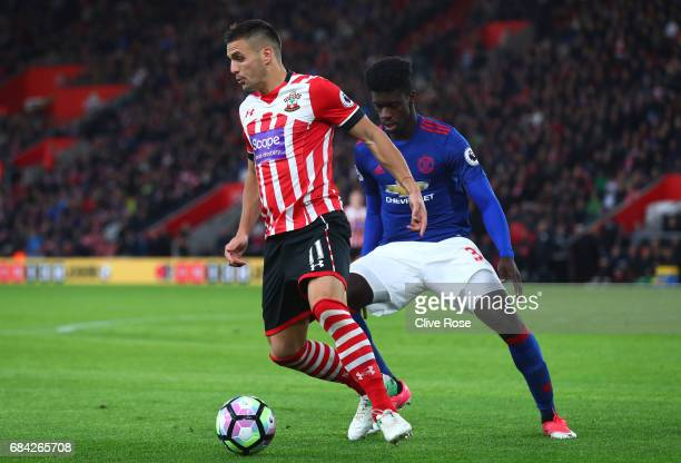 Dusan Tadic of Southampton is put under pressure from Axel Tuanzebe of Manchester United during the Premier League match between Southampton and...