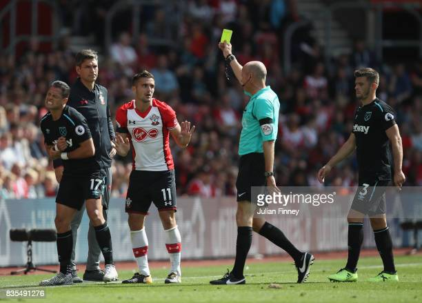 Dusan Tadic of Southampton is shown a yellow card by referee Lee Mason during the Premier League match between Southampton and West Ham United at St...