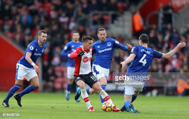 Dusan Tadic of Southampton is tackled by Michael Keane of Everton as Gylfi Sigurdsson of Everton looks on during the Premier League match between...