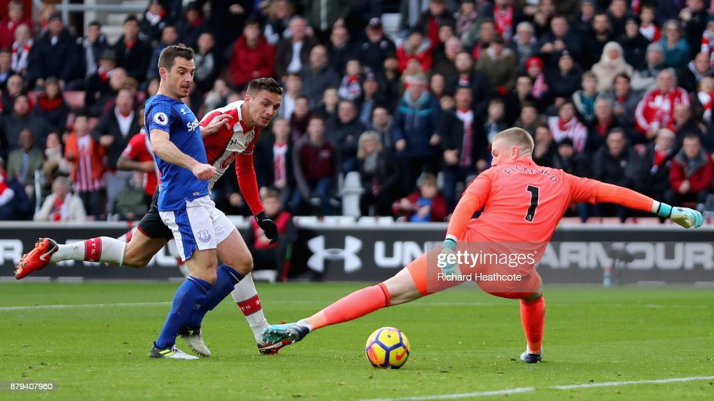 Dusan Tadic of Southampton scores the first Southampton goal past Jordan Pickford of Everton and Leighton Baines of Everton during the Premier League match between Southampton and Everton at St Mary's Stadium on November 26, 2017 in Southampton, England.
