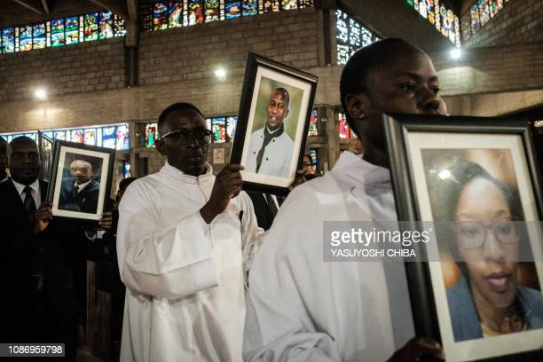 Dusit hotel and office complex employees hold portraits of their colleagues during a memorial service, on January 23 at the Consolata Shrine in...