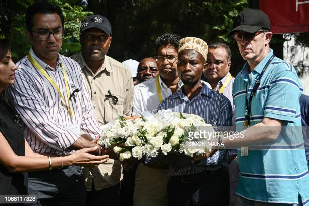 DusitD2 hotel General Manager Michael Metaxas , a survivor and the DusitD2 staff Abdullahi Ogelo place a wreath with other staff at the hotel's gate...