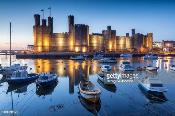 dusk at caernarfon castle - gwynedd stock photos and pictures