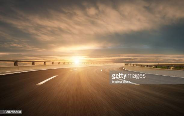 dusk colored clouds in the background, highway overpass curved approach bridge - light natural phenomenon stock pictures, royalty-free photos & images