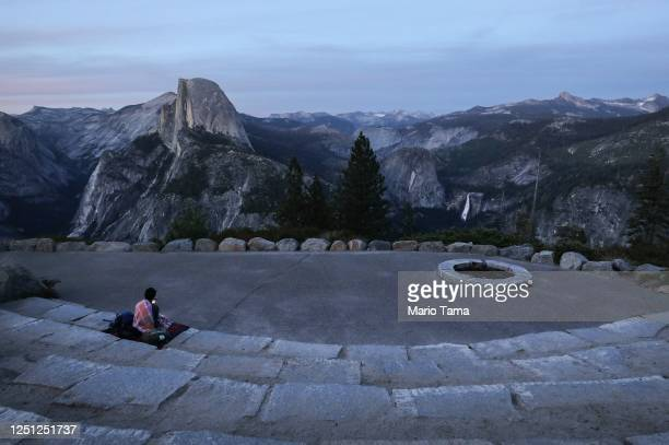 Dusk falls over Half Dome and Nevada Fall as a visitor sits on June 18, 2020 in Yosemite National Park, California. Yosemite National Park reopened...