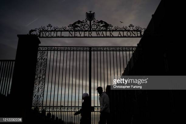 Dusk falls over The Shankly Gates at the home of Liverpool Football Club on March 13, 2020 in Liverpool, United Kingdom. It has been announced that...