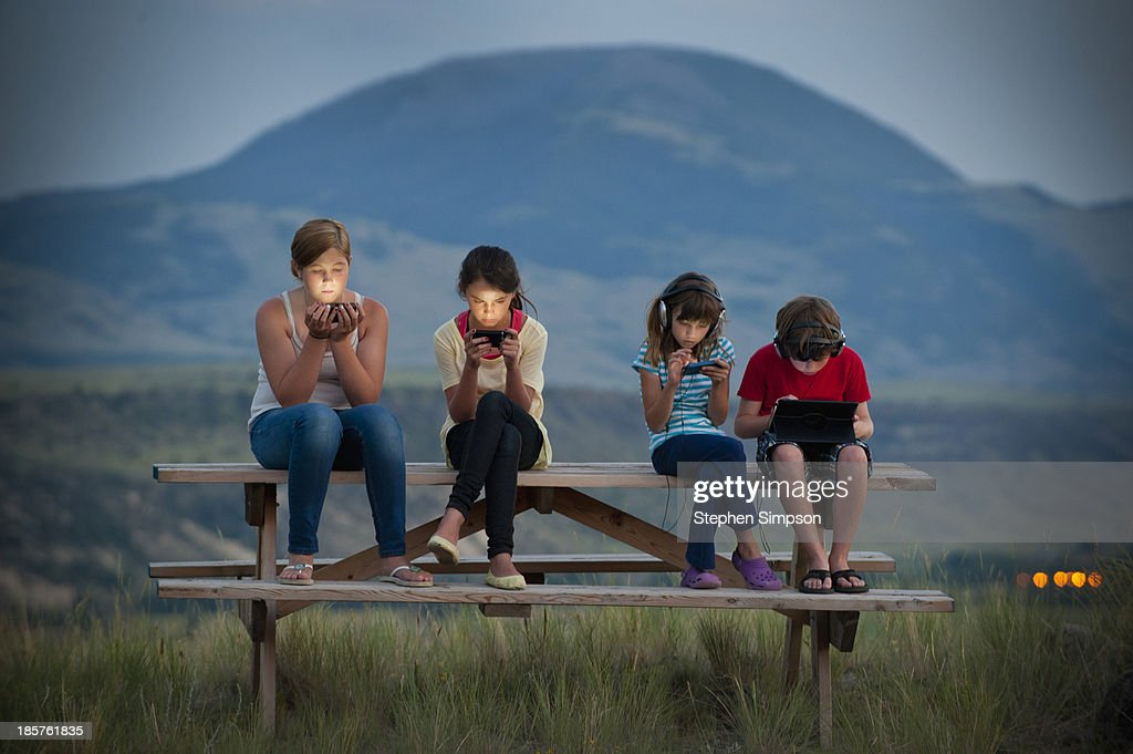 dusk, four kids on picnic table with tech/screens : Stock Photo