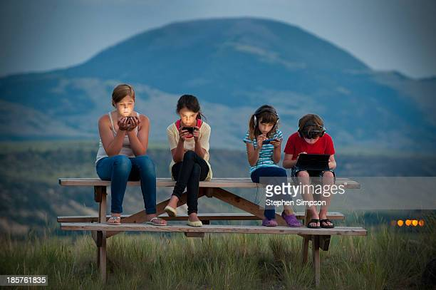 dusk, four kids on picnic table with tech/screens