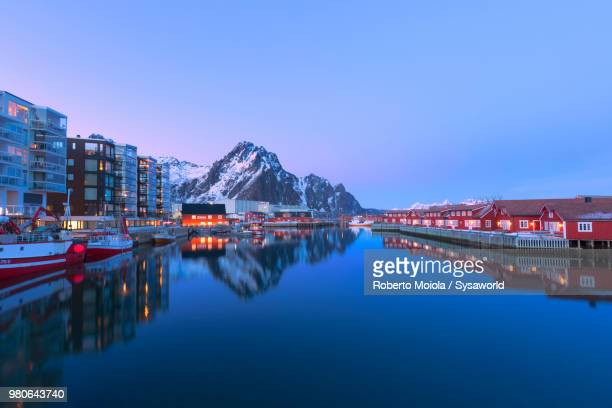 Dusk lights on traditional wood houses called Rorbu in the fishing village of Svolvaer surrounded by cold sea and snowcapped mountains, Lofoten Islands, Norway