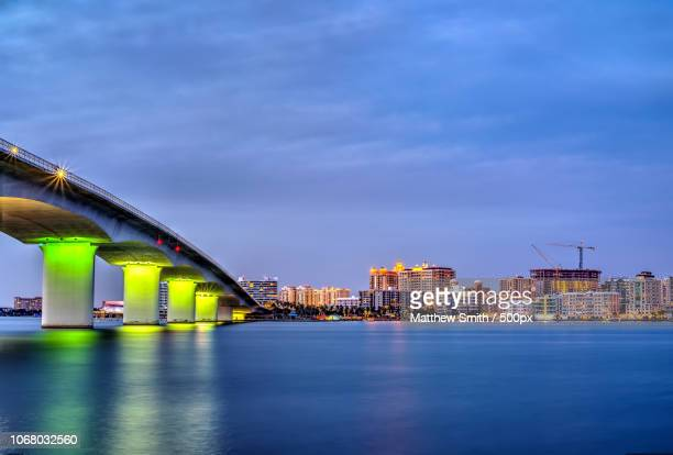 dusk over modern city with illuminated bridge - sarasota stock photos and pictures