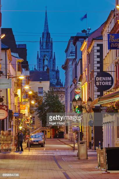 a dusk scene on robert morgan st with holy trinity church in the background, in downtown cork, ireland. - cork material stock photos and pictures