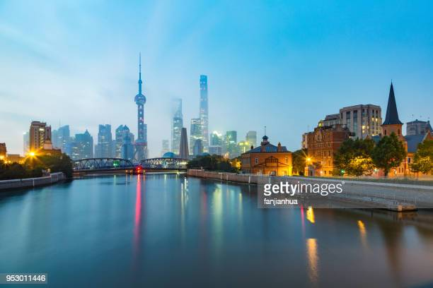 dusk view of the  oriental pearl tower with waibaidu bridge against sky - the bund stock photos and pictures