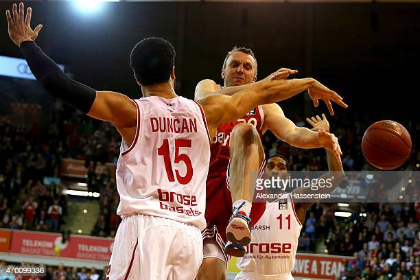 Dusko Savanovic of Muenchen is challenged by Joshua Duncan of Bamberg and his team mate Bradley Wanamaker during the Beko Basketball Bundesliga match...