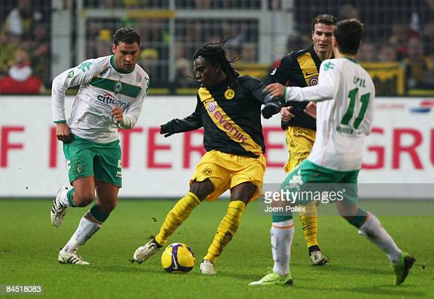 Dusko Tosic of Bremen and Mesut Oezil tackle Tinga of Dortmund during the round of 16 DFB Cup match between Borussia Dortmund and SV Werder Bremen on...