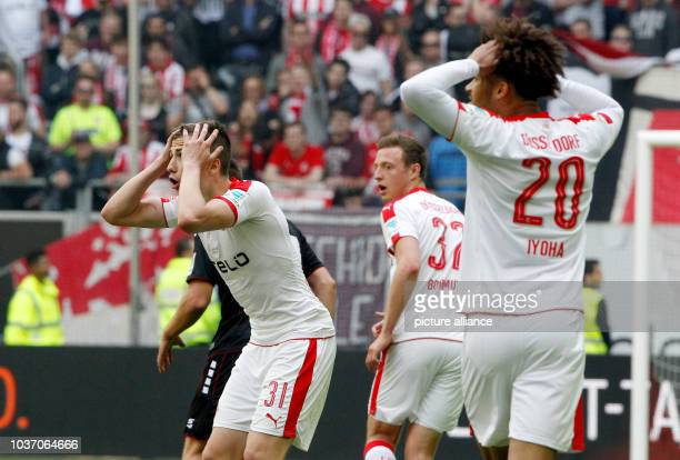 Dusseldorf's Marcel Sobottka Robin Bormuth and Emmanuel Iyoha raise their hands to their heads during the German 2 Bundesliga soccer match between...