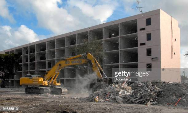 Dust and debris blow by as an excavator from BG Group Demolition moves metal and drywall scraps during the demolition of the former SFBC Drug Trial...