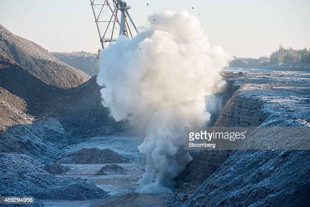 Dust and rock rises following a controlled explosion of oil shale on the pit floor at Eesti Energia AS's open pit mine in Narva Estonia on Wednesday...