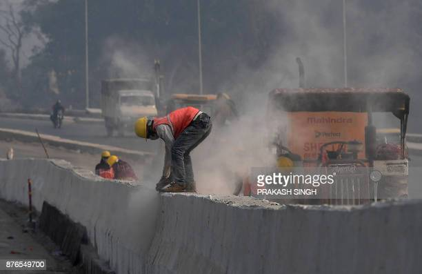 Dust billows as a worker grinds the concrete divider of an underconstruction flyover as vehicle drive through a smog covered New Delhi on November 20...