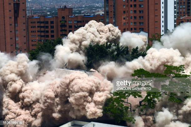 TOPSHOT A dust cloud engulfs the area during the demolition of the Monaco building which was once home to Colombian drug lord Pablo Escobar in...