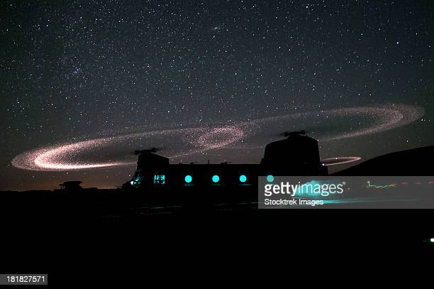 Dust lights up the rotors of a CH-47 Chinook helicopter.