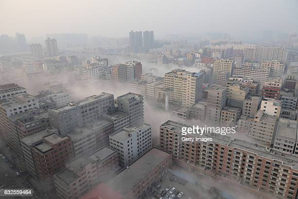 Dust rises following a controlled explosion of residential buildings on January 23, 2017 in Zhengzhou, Henan Province of China. The village in...