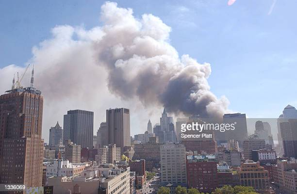 Dust swirls around south Manhattan after a tower of the World Trade Center collapses September 11 2001 in New York City after two airplanes slammed...
