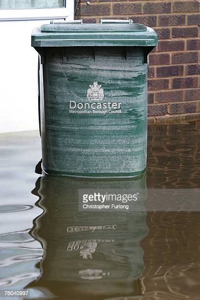 A dustbin shows water marks as the receding water is pumped away after severe flooding in the village of Toll Bar on July 5 near Doncaster England...