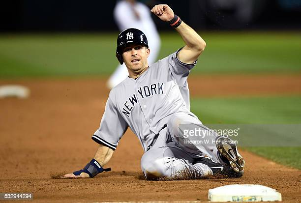 Dustin Ackley of the New York Yankees slides into third base safe against the Oakland Athletics in the top of the six inning at Oco Coliseum on May...