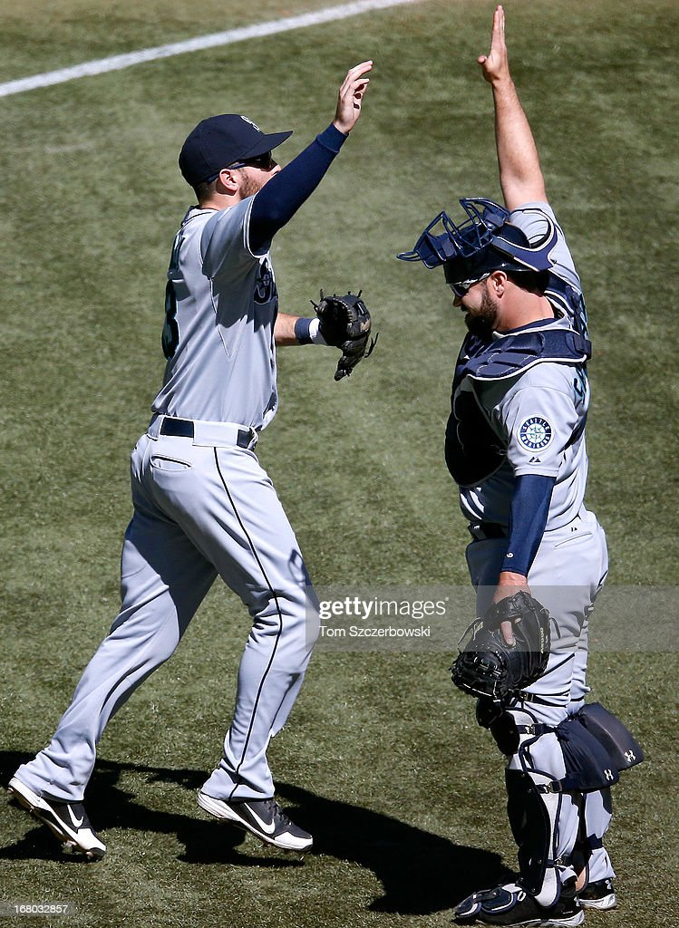 Dustin Ackley #13 of the Seattle Mariners celebrates with Kelly Shoppach #7 after their victory during MLB game action against the Toronto Blue Jays on May 4, 2013 at Rogers Centre in Toronto, Ontario, Canada.