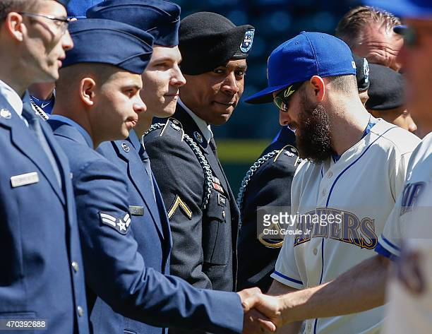 Dustin Ackley of the Seattle Mariners greets members of the US Military as they are honored as part of Salute to Armed Forces Day prior to the game...